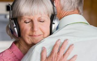 Signora che abbraccia marito mentre ascolta un brano audio
